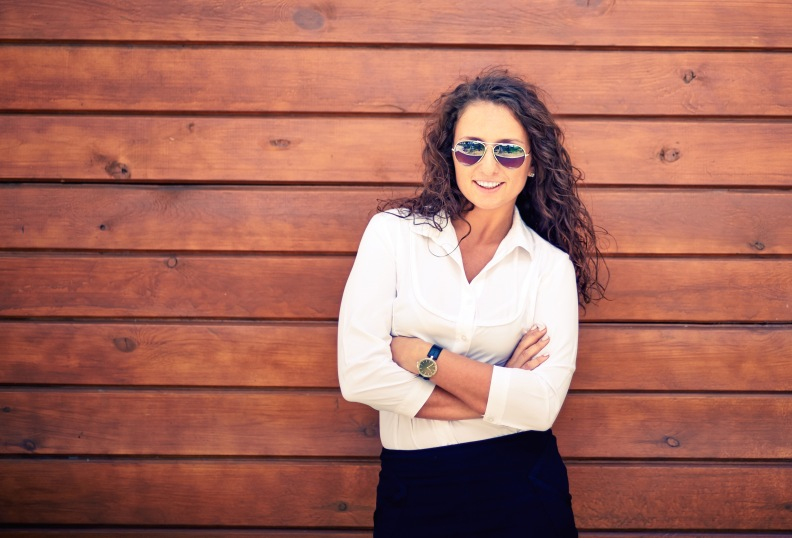 Image of attractive businesswoman in sunglasses looking at camera